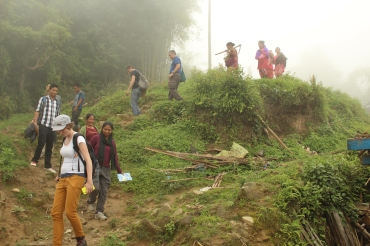 Photograph of villagers following the team down the hill